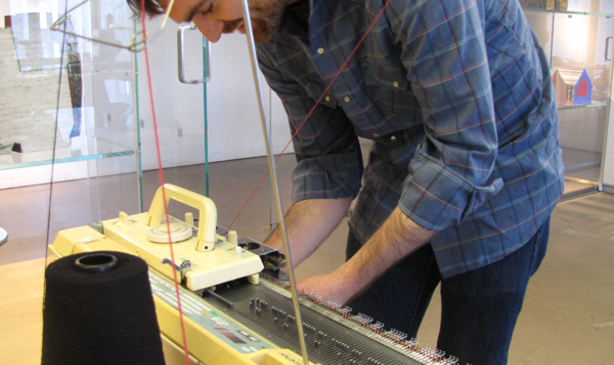 artist Andrew Salomone at work on his hacked knitting machine.