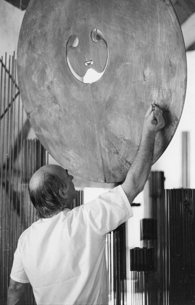 Bertoia using an implement he made to play a bronze gong