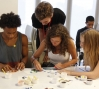 Otis helps participants with their mosaics.: Otis helps participants with their mosaics.